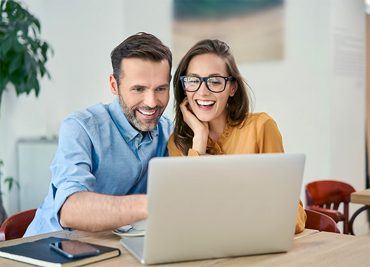 a man and a woman are on a laptop